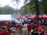 a grove of tailgaters with smoke from bratwurst frying