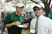two handsome young male alumni eating at a fraternity tailgate party