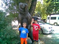 two young boys posing in fron of a large scarey wooden bear