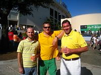 three alums in school colors posing outside the stadium