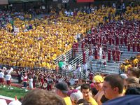 Student section of thousands in stands wearing yellow Ts