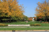 A BU long low sign in the main quad showing fall trees and acres of lawn