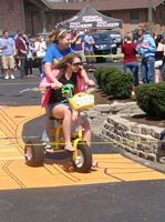 two gals ride a trike in a campus race