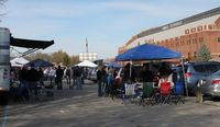 massive expanse of blue taents and tailgaters in lot by fieldhouse