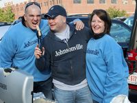 two men and a woman in Johnsonville sweats in Butler Colors with one man feeding a brat to another