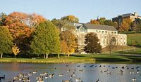 Colgates lake is full of ducks and the campus is in the background