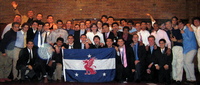 Beta Theta Pi guys pose with chapter (red and blue) flag