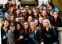 Thetas all smile in navy sweatshirts posing on their house steps