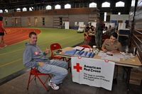 ROTC Blood Drive has guy sitting at table in the fieldhouse with a gal in uniform filling out more paperwork