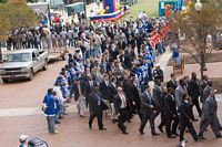 Duke team, dressed in suits and ties, walk through the fans on way to stadium