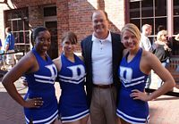 three pretty duke cheerleaders pose with fans before the game