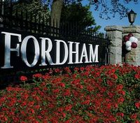 The landscaped flowered sign spelling out FORDHAM in white above red flowers.