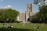 Students relax in a lawn with a tall towered gothic stone building in the backgraoun.