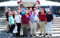 20 older alums pose outside a tailgate tent