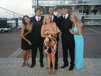 Fijis and dates pose in formal wear by a river boat.
