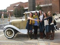 "5 gals pose in front of the gold car ""The Ramblin Wreck""."