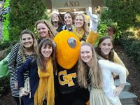 a dozen beautiful Alpha Chis pose with the yellow jacket mascot.