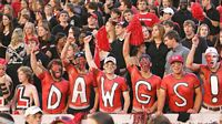 "Male undergrads in red body paint with white and black letter spelling out ""DAWGS""."