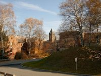 The Holy Cross campus sits above you as you look through the beautiful colorful fall trees.  There are stately brick b uildings with their towers and peaks.
