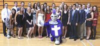 3 dozen campus leaders, dressed up in suits and dresses, pose with the Crusader mascot.