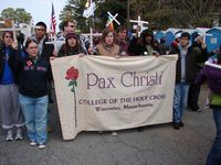HC students bearing crosses march behind a Pax Christi banner.