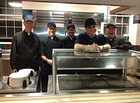 5 jesuit brothers that are running the mid night breakfast line in their cooking attire.