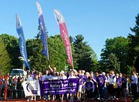 Huge relay for life gathering for cancer by Holy Cross students walking behind a purple banner with banners waving high.