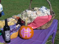 There is a bottle of purple wine and a pumpkin carced and painted with a HC logo on it.