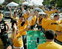 Here are a dozen yellow clad alumni playing beer pong in the tailgate area.