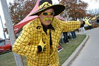 This fan is dressed in a yellow checked suit, black shirt, yellow tie, yellow wide brim hat, yellow died mustash, yellow gloves and dark glasses.  Wow!