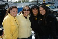 4 ladies gather and smile for the camera in the tailgating area.