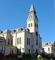 This is a stately steepled white limestone three story building with chimes in the steeple.
