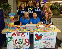 Alpha Xi Delta has a charity sale and the girls here are seated at the sales table on campus.