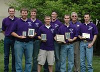 K States nationally awarded crop team poses with purple shirts and holding plaques.