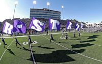The cheerleaders are leading the team out before the kickoff and spelling out K State in flags.