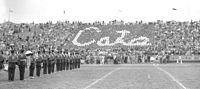 This is a black and white photo of the old stadium with a card section spelling CATS while the band plays on the field.
