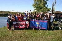 Missouri State and KU water ski teams pose together on the shore.