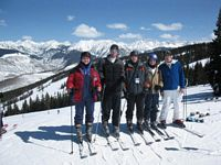 5 members of the ski team are on top of a western mountain posing with good snow against a beautiful blue sky.