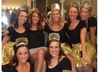 8 members of Kappa Kappa Gamma pose in countumes as fairy princeses.  Their clothes are black and gold and they are raising money for their foundation.