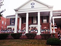 The sigma Kappa house is red brick whith white pillars.  30 of the pretty coeds are posing on the porch.