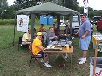 Here a group of 6 alumni are tailgating under a tent in the grass lot.