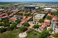 This aerial view of campus begins near the tower and has Tiger Stadium in the far distance.  The roofs seem to be red tile..