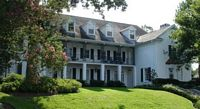 The Z T A house is a georgious three story white frame mansion with pillars.