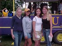 4 undergrad gals pose in front of a purple train engine all wearing LSU colors.