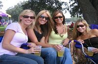 4 lovely young alumnae smile at you in their shady tailgate spot.