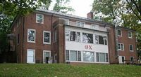 3 story Theta Chi house is red brick.