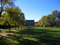 A view up the lawn on the open quad with a stately brick building at the end of the long lawn.