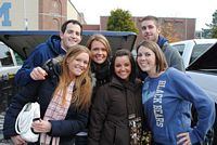 3 young alumni couples pose at their tailgate with the trunk lid up.