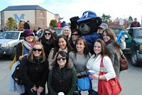 9 pretty girls pose with the Black Bear mascot.