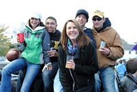 5 young alums, bundled up, take time out from pitching a football to have an adult beverage and smile at you.